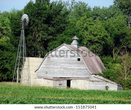 dilapidated old building white barn with windmill - stock photo