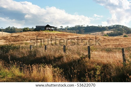 Dilapidated old farm house behind an old wire fence - stock photo