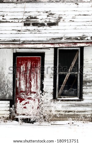 Dilapidated old farm house in winter - stock photo