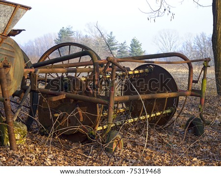 dilapidated old farm machinery in a rural landscape