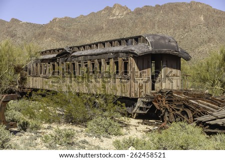 Dilapidated old railroad car deteriorating near rocky mountain in southern Arizona desert - stock photo