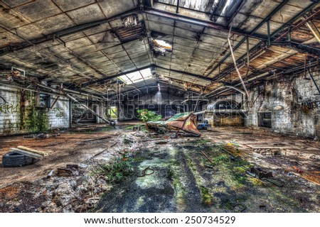 Dilapidated warehouse in an abandoned factory, HDR - stock photo