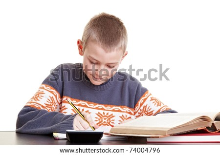 Diligent boy working on his homework at his desk - stock photo