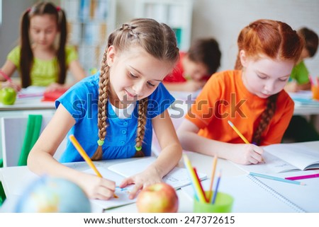 Diligent girls drawing with crayons at lesson - stock photo