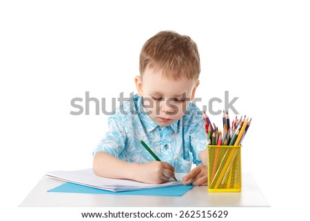 Diligent little boy draws with crayons isolated on white background