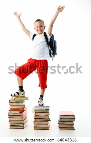 Diligent preschooler standing on the top of book stairs with his arms raised