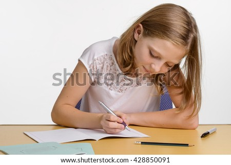 Diligent pupil during studying and preparation for school subjects. Accurate young girl writes in the copybook and looks on paper. - stock photo