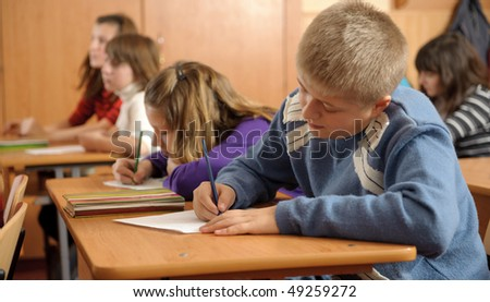 Diligent schoolboy is writing down in notebook during lesson - stock photo