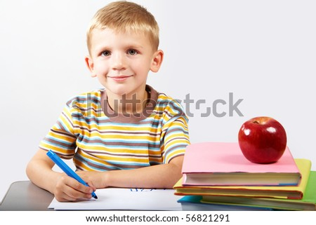 Diligent schoolboy looking at camera during drawing