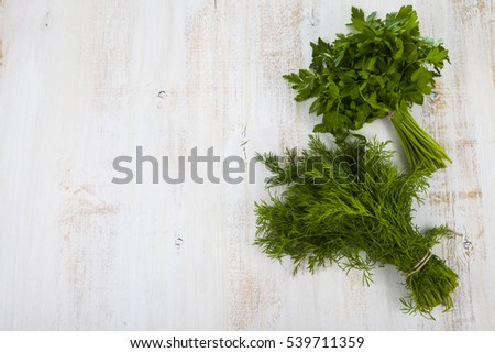 Dill and parsley on a light wooden table. Herbs closeup.