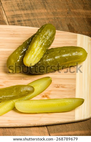 Dill pickle spears on cutting board - stock photo