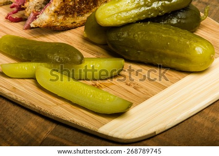 Dill pickle spears on wooden cutting cutting board - stock photo