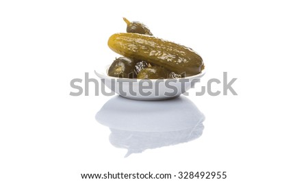 Dill pickles in a white bowl over white background - stock photo