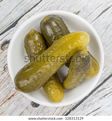 Dill pickles in a white bowl over wooden background - stock photo