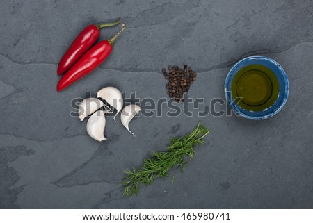Dill, red peppers, black pepper corn, oil and garlic on a grey slate plate, stock picture