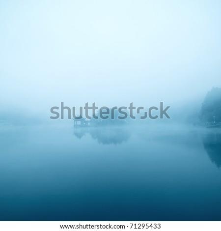 dim lake in the fog - stock photo