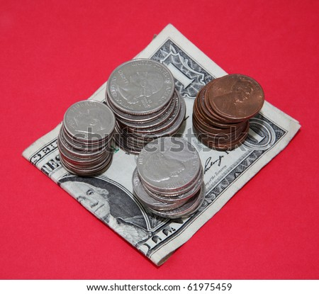 Dimes, quarters, cents and nickels piled on a dollar bill on red background