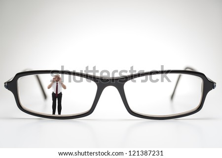 Diminutive elderly man peering through a lens on a pair of spectacles or prescription glasses , a humorous take on aging eyesight requiring corrective glasses - stock photo