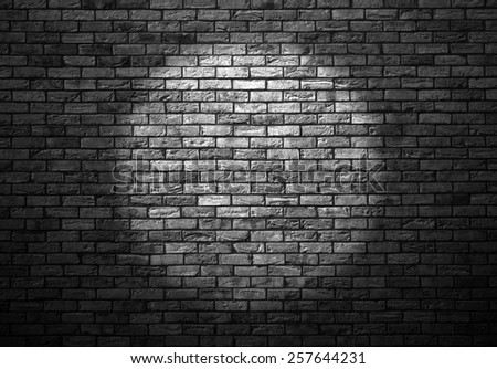 dimly lit old brick wall enlightened cone of light - stock photo
