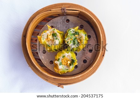Dimsum in the steam basket . Chinese dimsum bamboo steamer isolated on white background. - stock photo