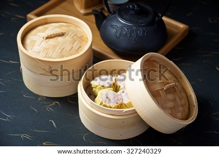 Dimsum set in bamboo container with teapot on black ground