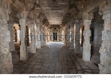 Dindigul, India - October 23, 2013: Inside the abandoned ruinous Shiva Temple on the Rock in Dindigul. Mandapam of stone pillars and ceiling leading to the inner sanctum. Beiges and Browns.