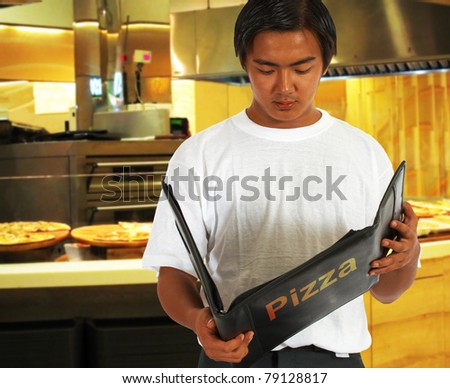 Diner Selecting Food From The Pizza Menu At A Pizzeria - stock photo