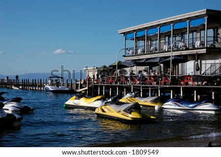 Diners eating at an outdoor restaurant near a jet ski rental business on a lake