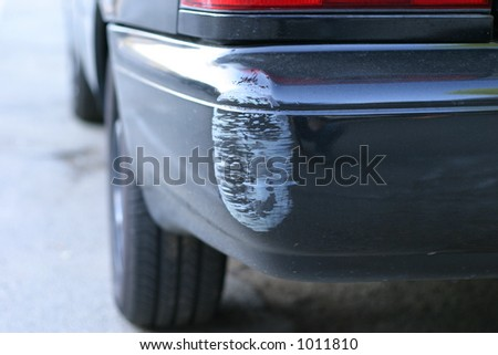 Dinged bumper on black car - stock photo