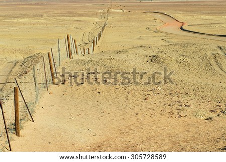 Dingoe fence in the Australian Outback. The fence is 9600 kilometers long, it keeps the dingoe dogs out of the areas, where the sheep graze. - stock photo