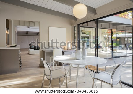 Dining area with round white table, hardwood floor, desk, copy space for art work and large glass sliding doors with walkout deck.  - stock photo
