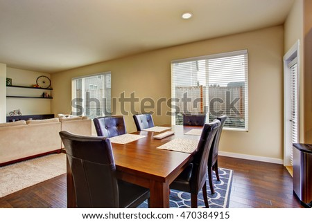 Dining area with wooden table set and leather chairs. Connected to living room. Northwest, USA