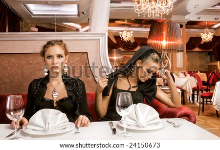 Dining Beauties. A portrait of two beautiful women on a table of a luxurious restaurant, for dinner. - stock photo