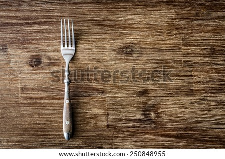 Dining fork on rustic vintage wooden table - stock photo