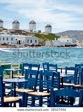 Dining in mykonos at seaside. Behind the famous windmill of mykonos - stock photo