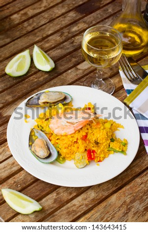 Dining  -  plate with seafood paella and glass of wine - stock photo