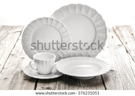 dining porcelain set of plates and one cup with ornament on wooden background, product photography - stock photo