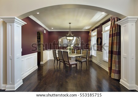 Dining room in luxury home with maroon walls.
