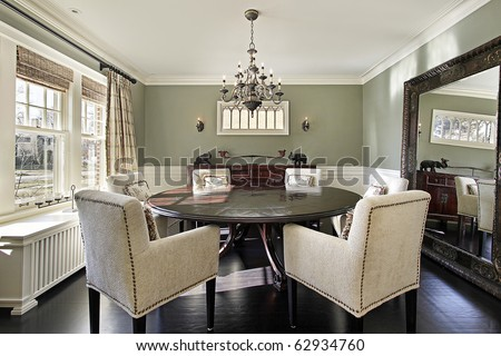 Dining room in luxury home with olive walls - stock photo