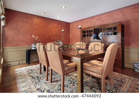 Dining room in luxury home with orange walls - stock photo