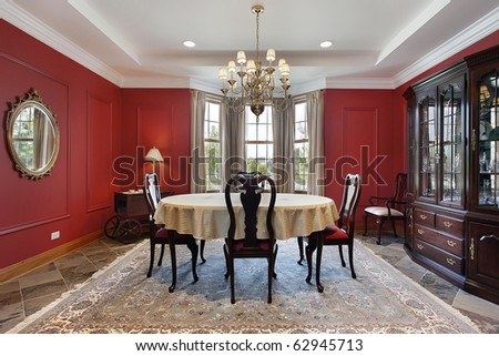 Dining room in luxury home with red walls - stock photo