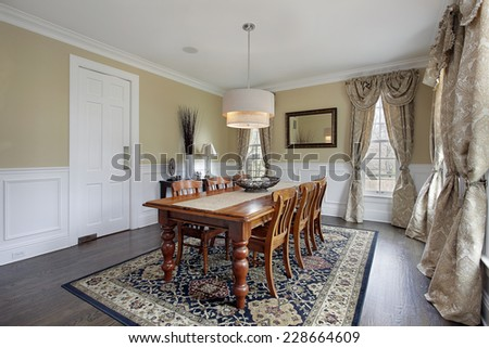 Dining room in luxury home with tan walls - stock photo