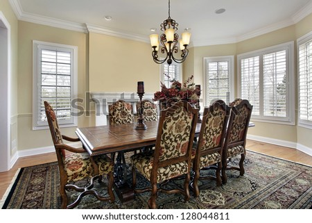 Dining room in luxury home with white fireplace - stock photo
