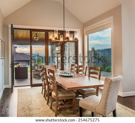 Dining Room in New Luxury Home with View of Patio and Colorful Sky  - stock photo