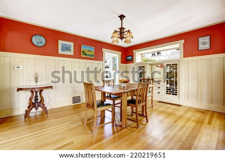 Dining room in old house with red and white wall trim. Furnished with old wooden table set and antique small table. - stock photo