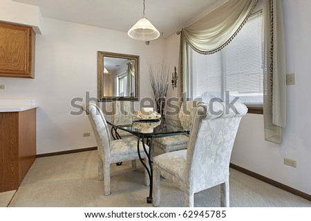 Dining room in townhouse with white fabric chairs - stock photo