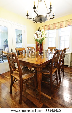Dining room interior with antique wooden table and chairs in house - stock photo