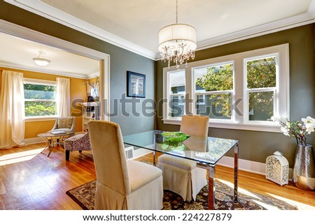Dining room interior with dark grey walls and hardwood floor. Table with glass top and two elegant chairs