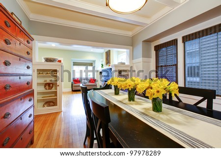 Dining room interior with large black table and wood dresser with grey blue walls. - stock photo