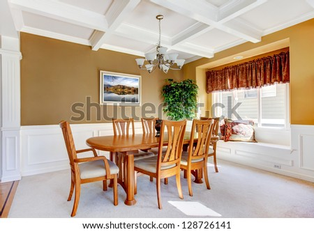 Dining room interior with white bench and wood table. - stock photo